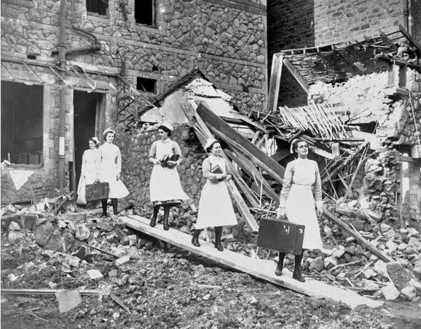 Nurses leaving the wrecked nurses home of CRI with their salvaged processions following an air raid
